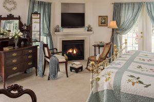 Sitting area with antique chairs and book in front of fireplace by quilted bed