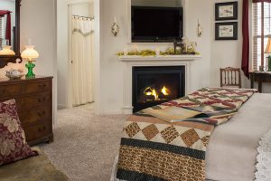 Bed with quilt across from roaring fireplace and bathroom entrance.