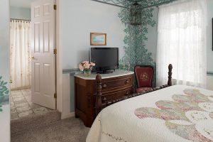 Bed across from TV next to wine and bathroom door