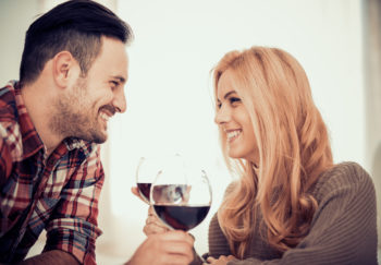 Couple smiles at each other over wine