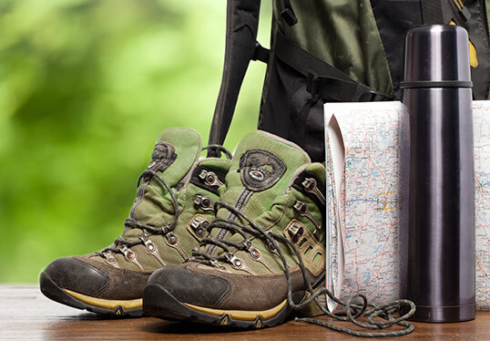 Pair of hiking boots by map, water bottle and backpack