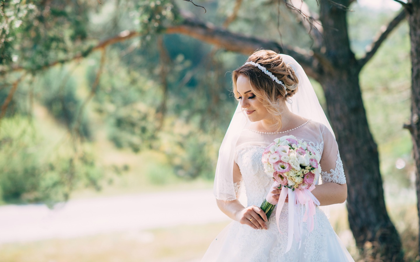 Bride smiles while walking past tree