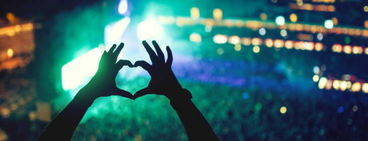 Fingers make heart shape in front of stage at live concert