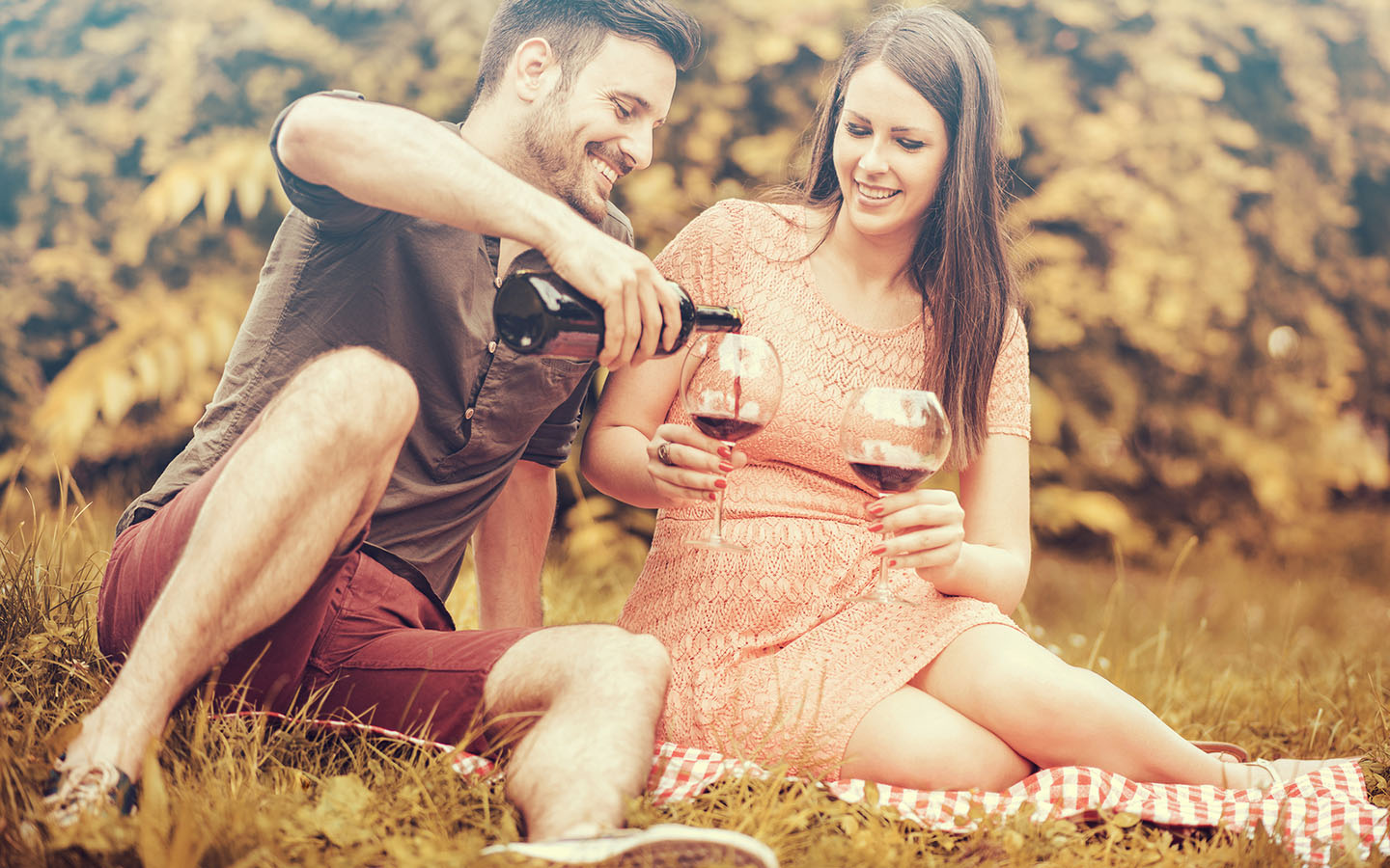 Couple in the fall with wine