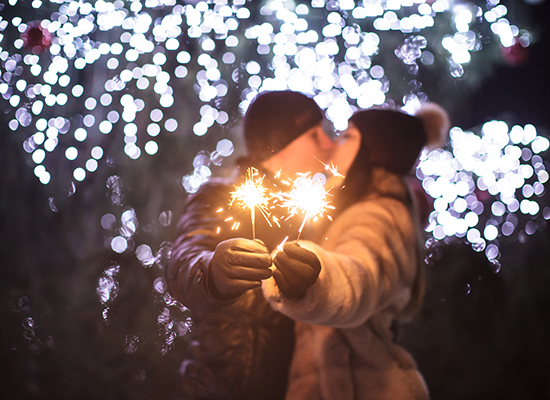 Couple kissing in front of Christmas lights with sparklers