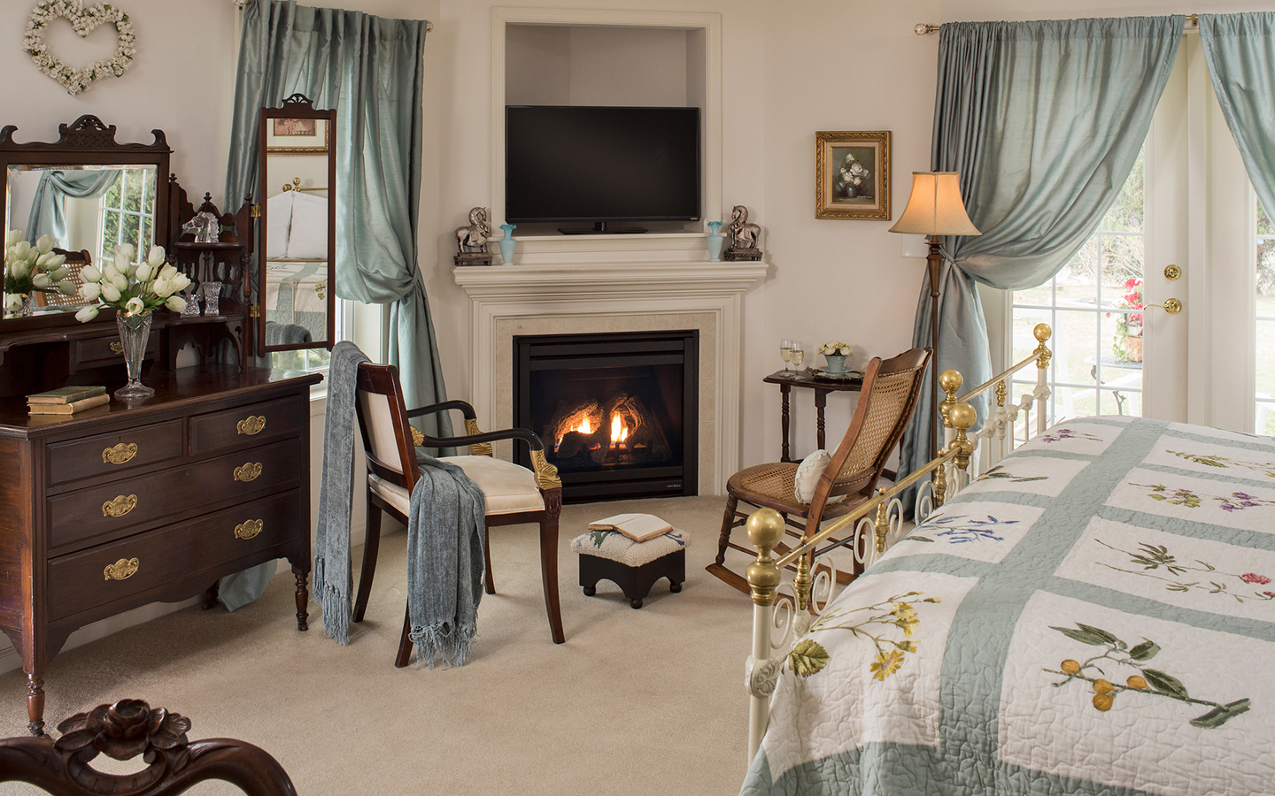 Sitting area with antique chairs, book, wine, and fireplace by quilted bed