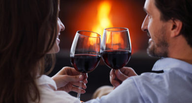Couple smiles at each other and toasts wine glasses in front of the fire