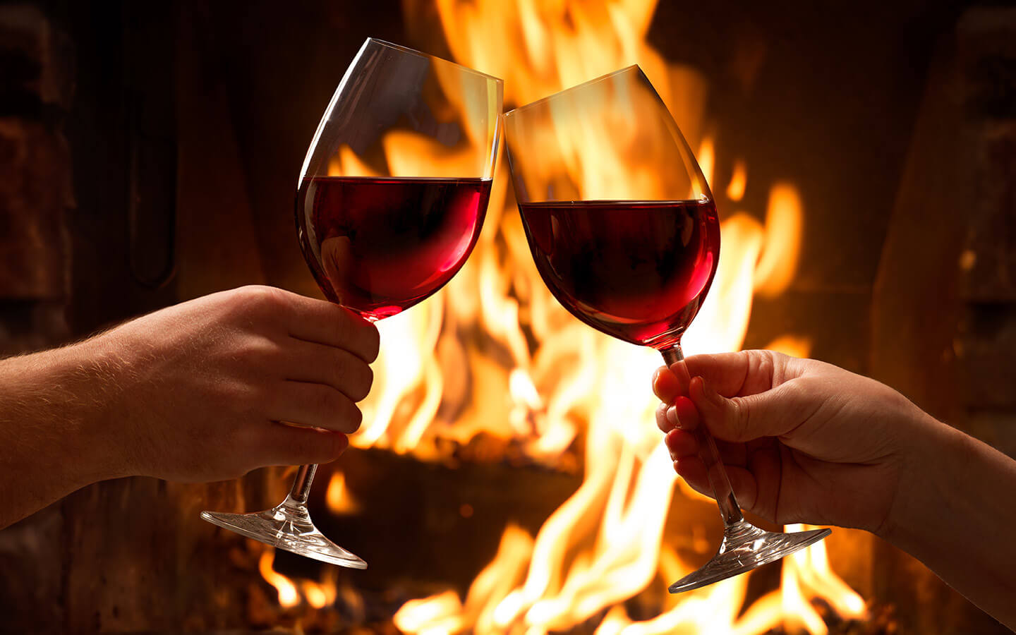 Toasting wine glasses in front of fireplace