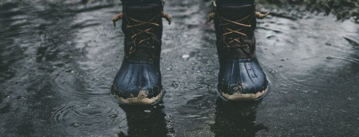 Person with rain boots standing in puddle next to unkempt grass