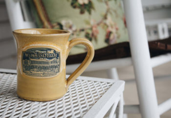 "Close-up of a cup reading ""The Inn at Westwynd Farm"" which sits on small table on porch"