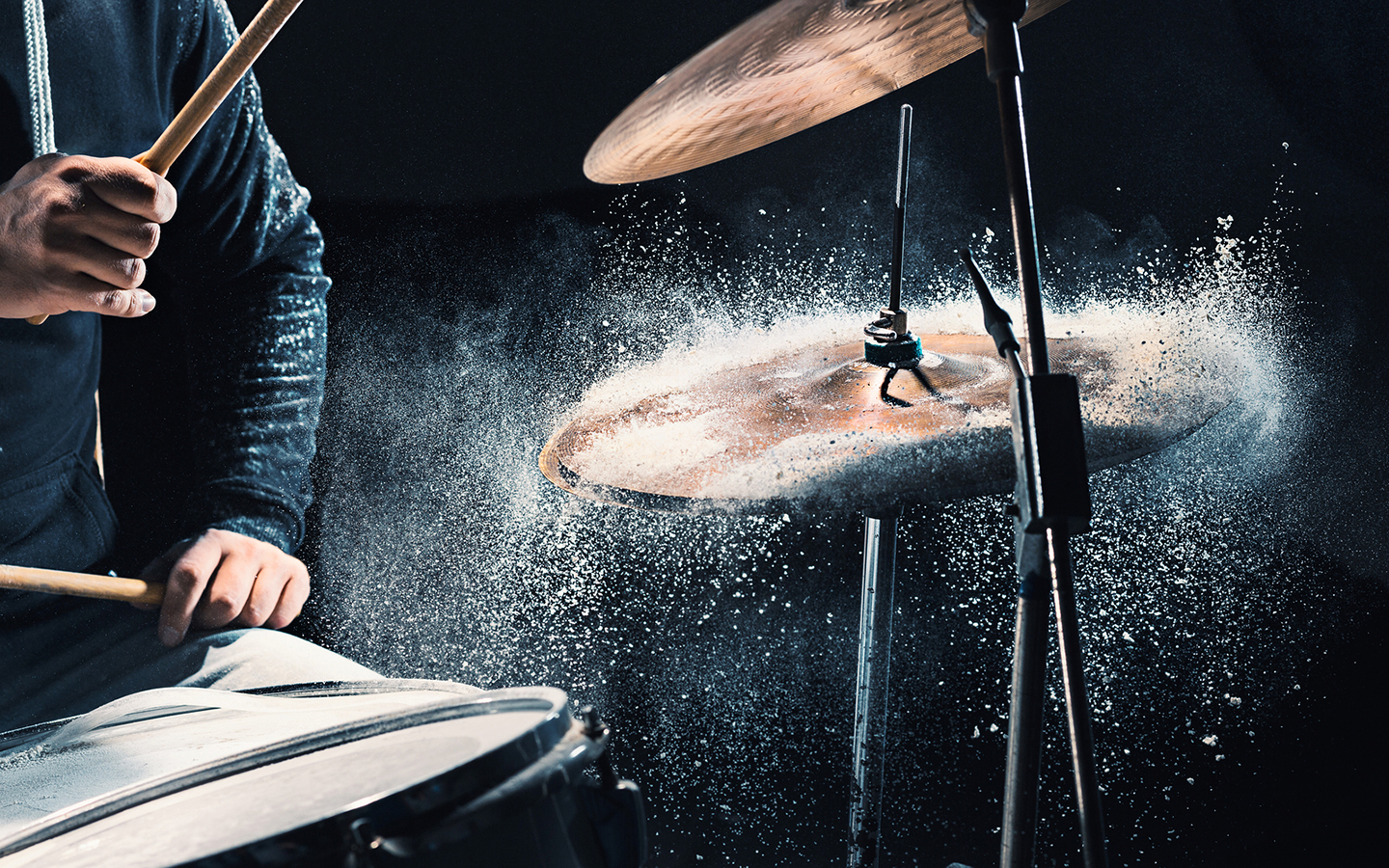 Man playing cymbal covered in flower, which sprays everywhere when he hits the cymbal