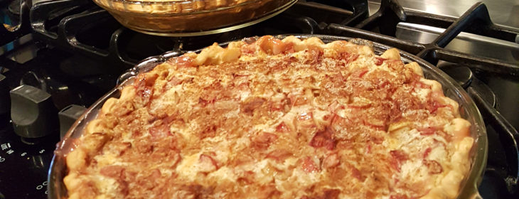 Fresh rhubarb pie sits in a pan on the stove