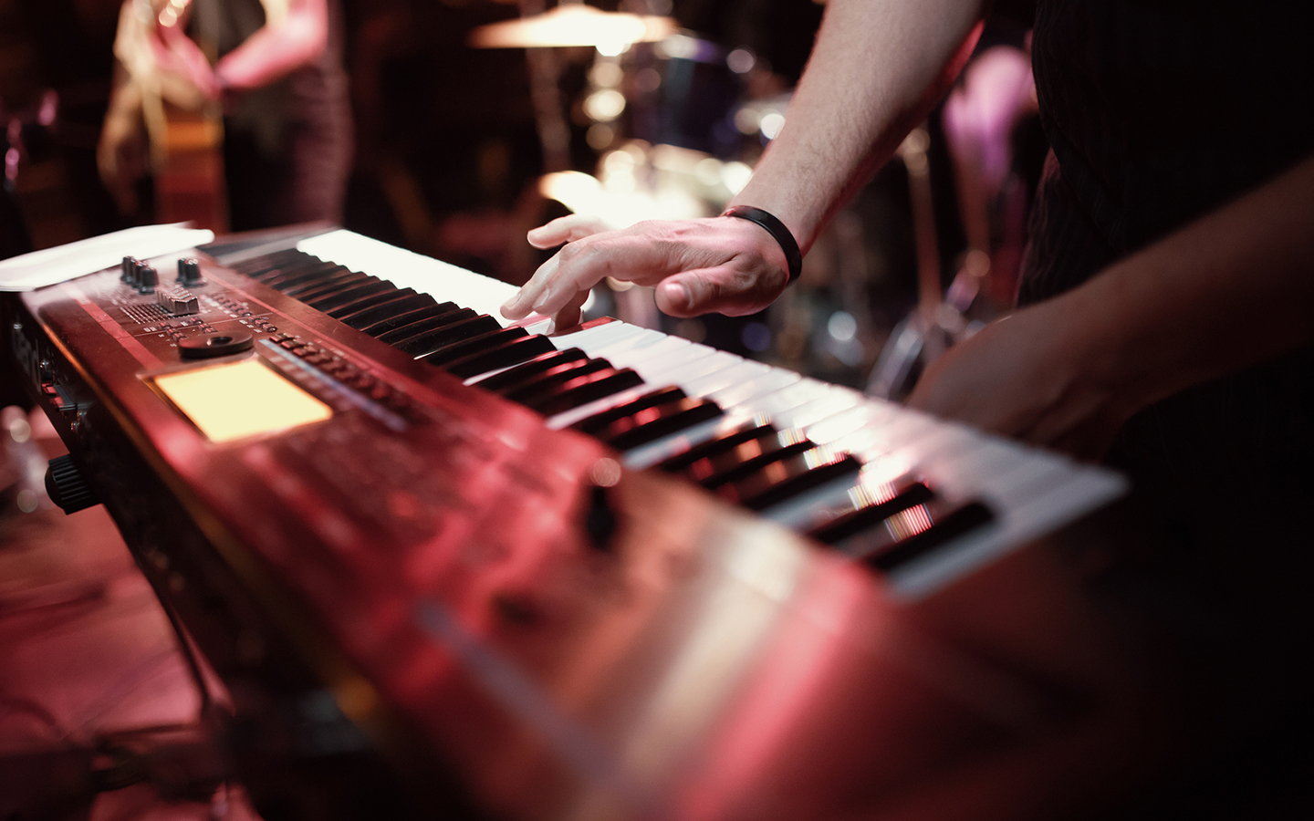 Hand playing keyboard on stage at a concert