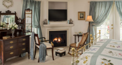 Sitting area with vintage chair and rocking chair in room with bright blue curtains and quilted bed