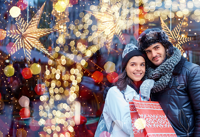 Man and woman bundled up in winter gear shop for Christmas presents in a well-decorated, bright shopping center