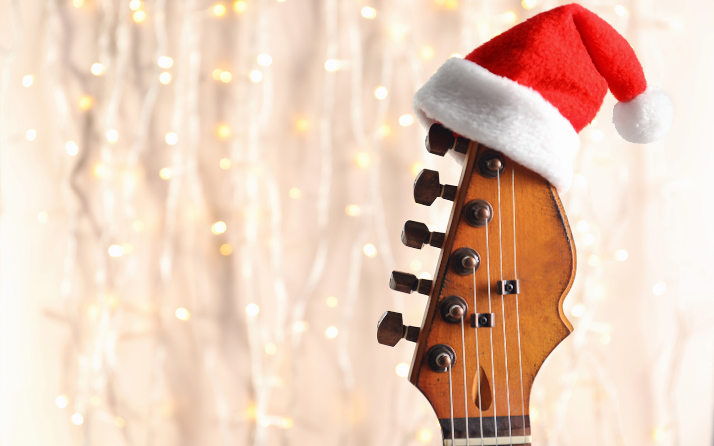 A guitar topped by a santa hat sitting in front of a string of lights
