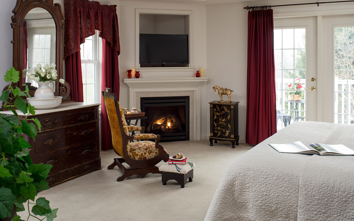 A comfortable antique bed and antique chair sit next to a warm fireplace
