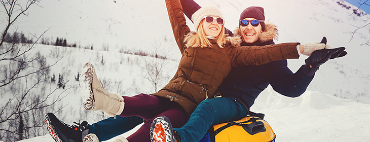 Couple grins while riding inner tube sled down slope together