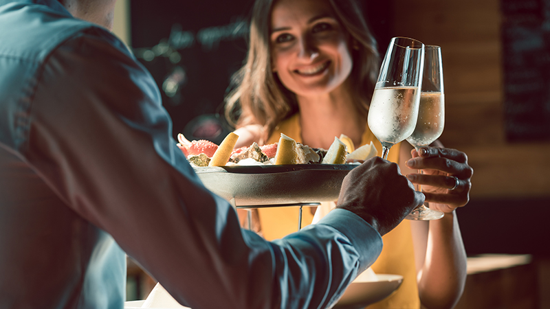 Man and woman at restaurant with plates of food and glasses of wine