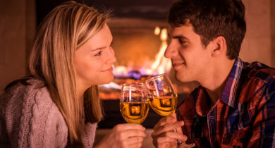 A happy young couple smile at each other while toasting wine glasses in front of the fire