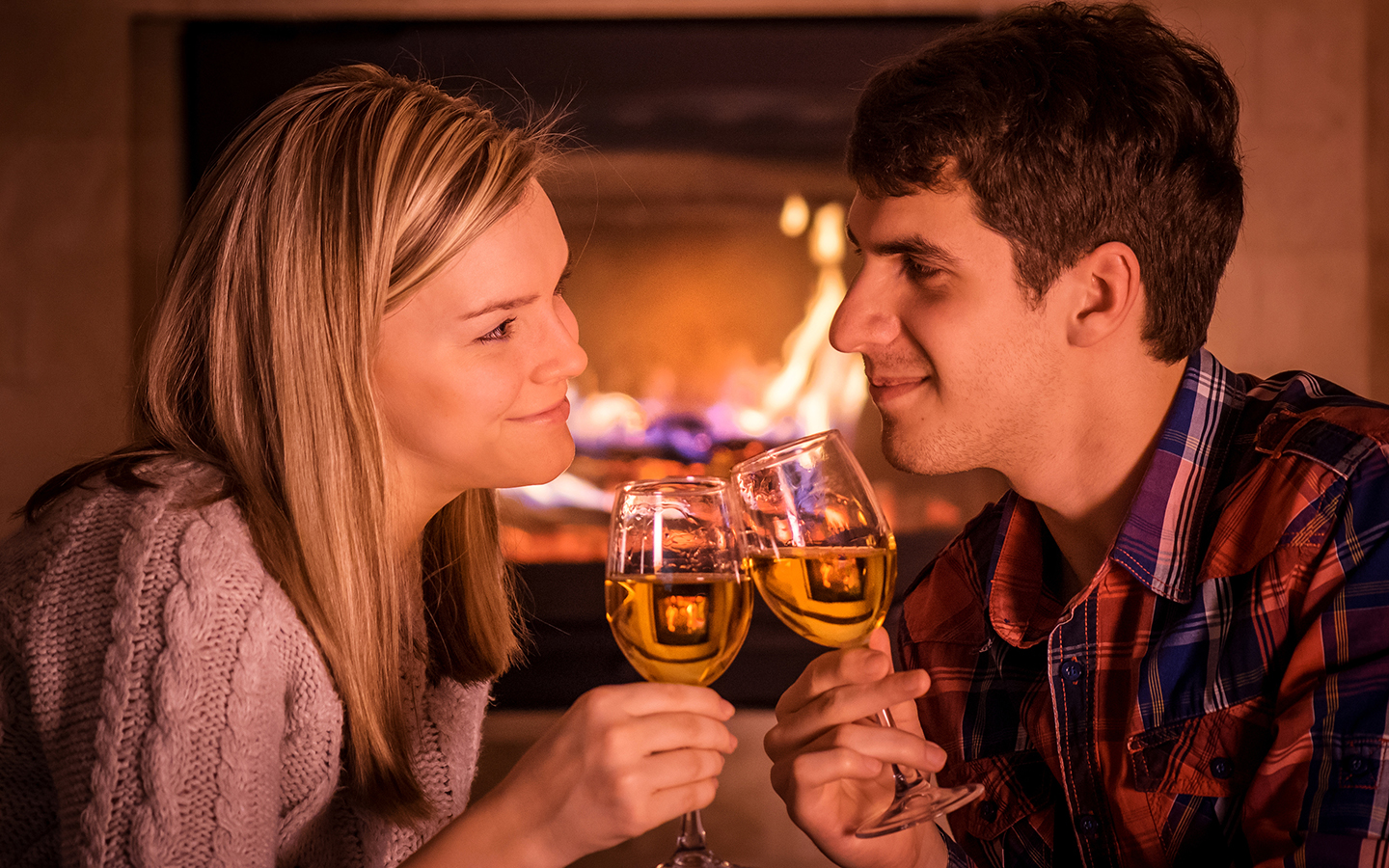 Woman and man clink wine glasses in front of fireplace