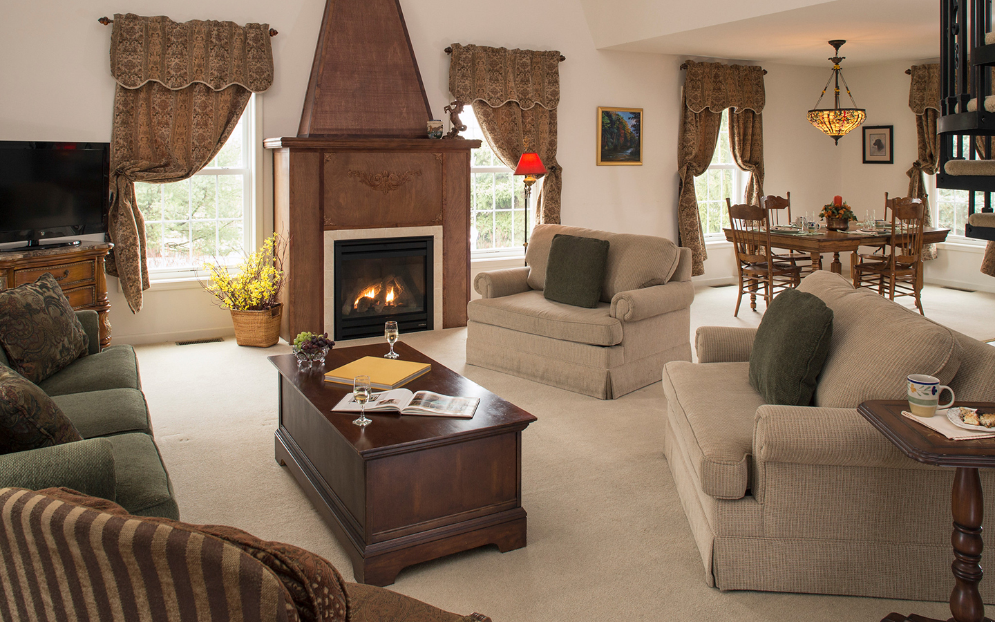 Sitting area with large, soft couches, wine glasses and a warm fireplace in Hershey, PA bed and breakfast