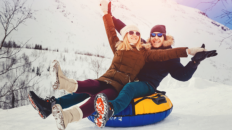 Man and woman on inner-tube in the snow