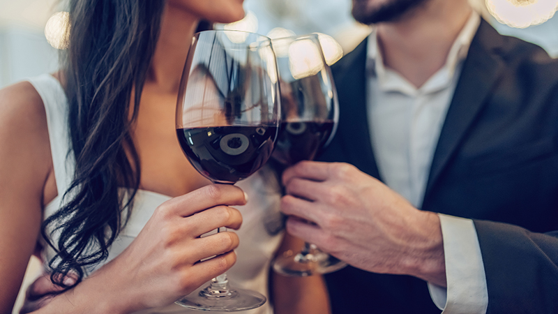Woman and man clink with glasses of wine