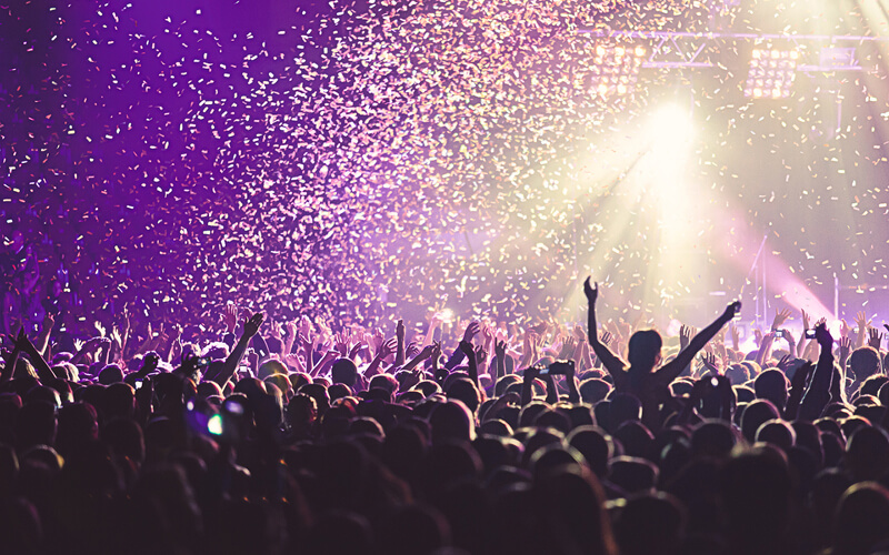 Crowd at a concert with purple lights and confetti in the air