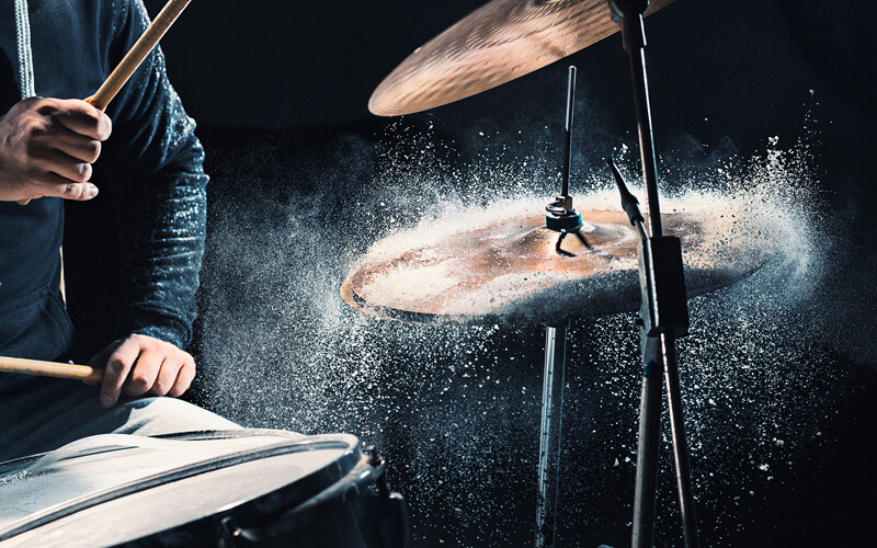 Mans arms playing the drums with water spashing off