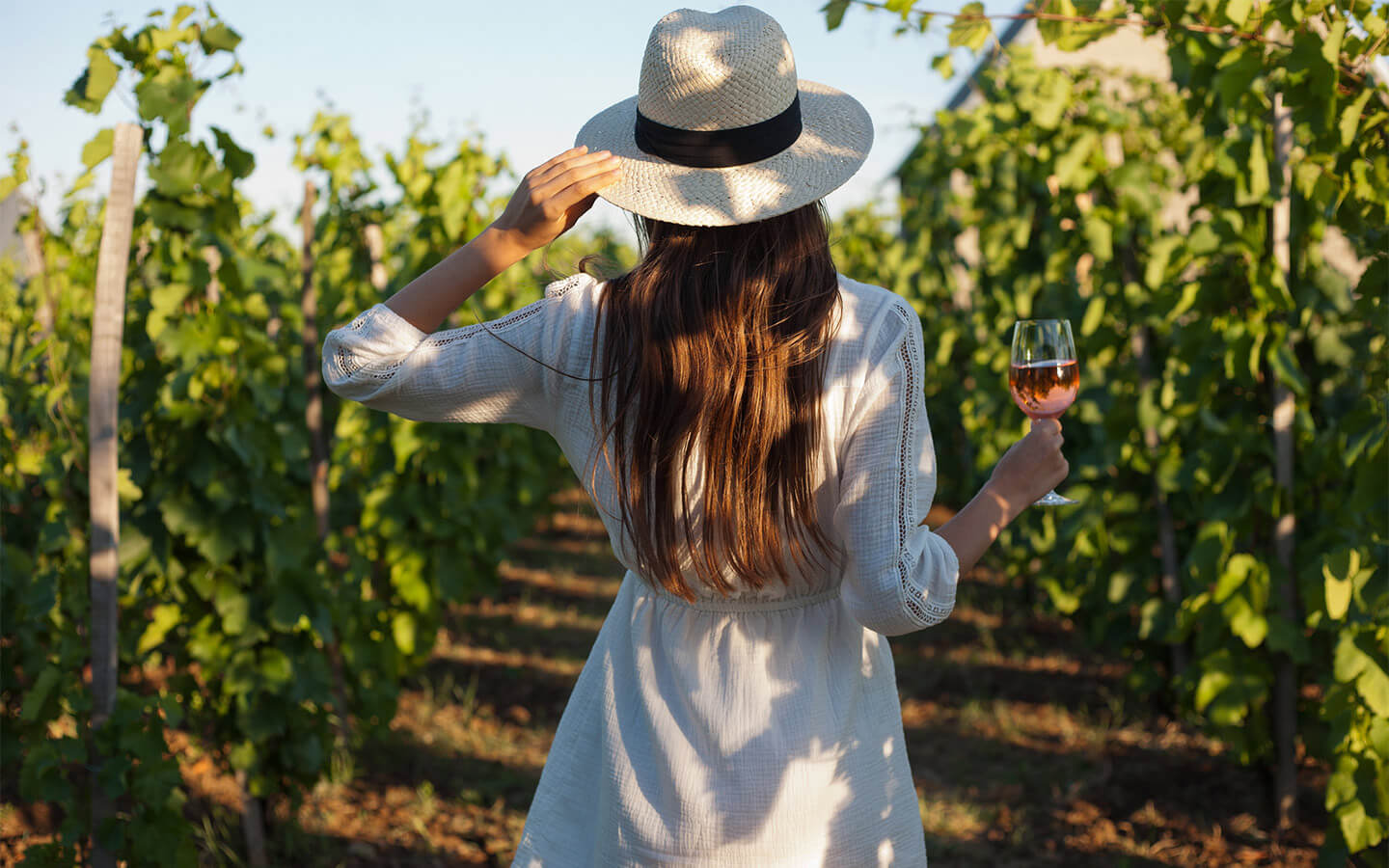 woman holding a glass of wine in a field