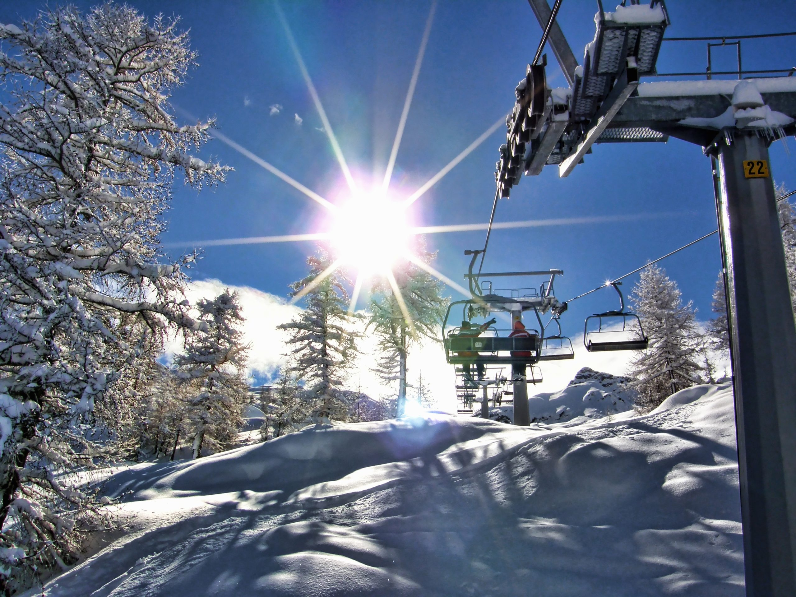 Ski life during winter with sun shining through brilliant blue sky
