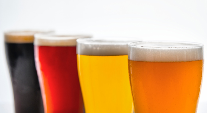 Flight of beer with four glass of beer in shades of gold, amber and deep cinnamon