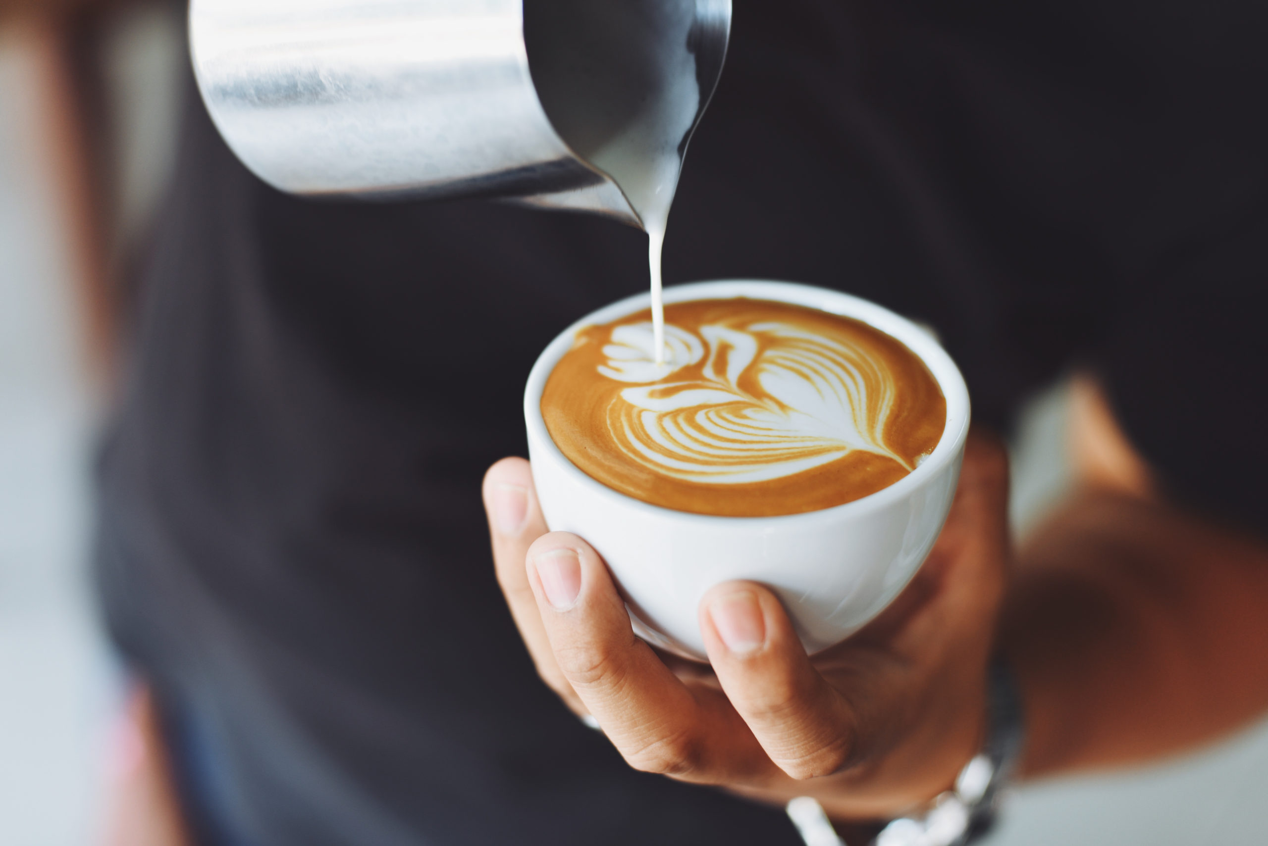 Barista making a latte and a frothy design