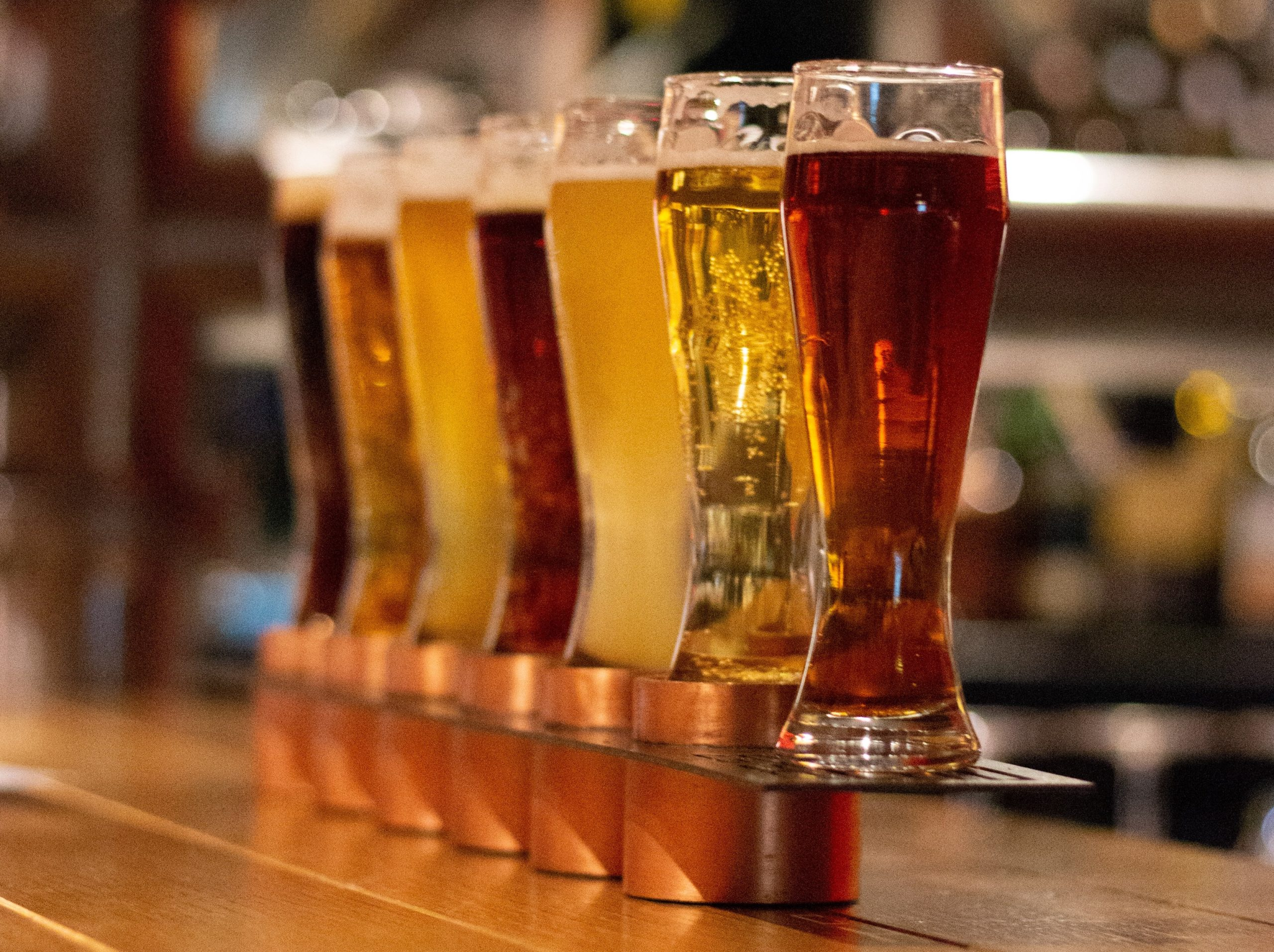 Flight of different colored ales on a wood bar corner
