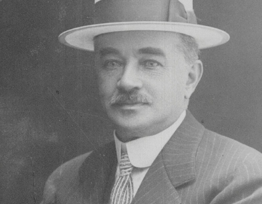 Milton Hershey with mustache wearing pin-striped suit, striped tie, and hat with band