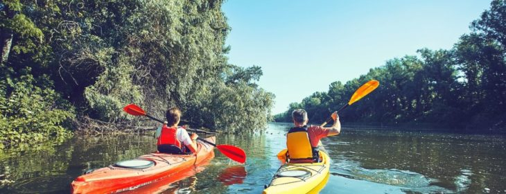 Couple kayaking down the river surrounded by lush greenery