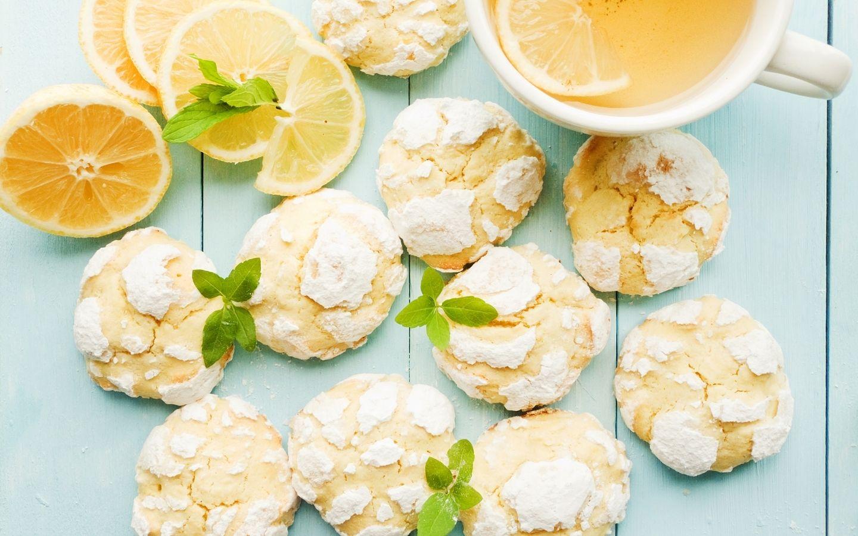 Powdered lemon cookies with cup of lemonade and slices of fresh lemon
