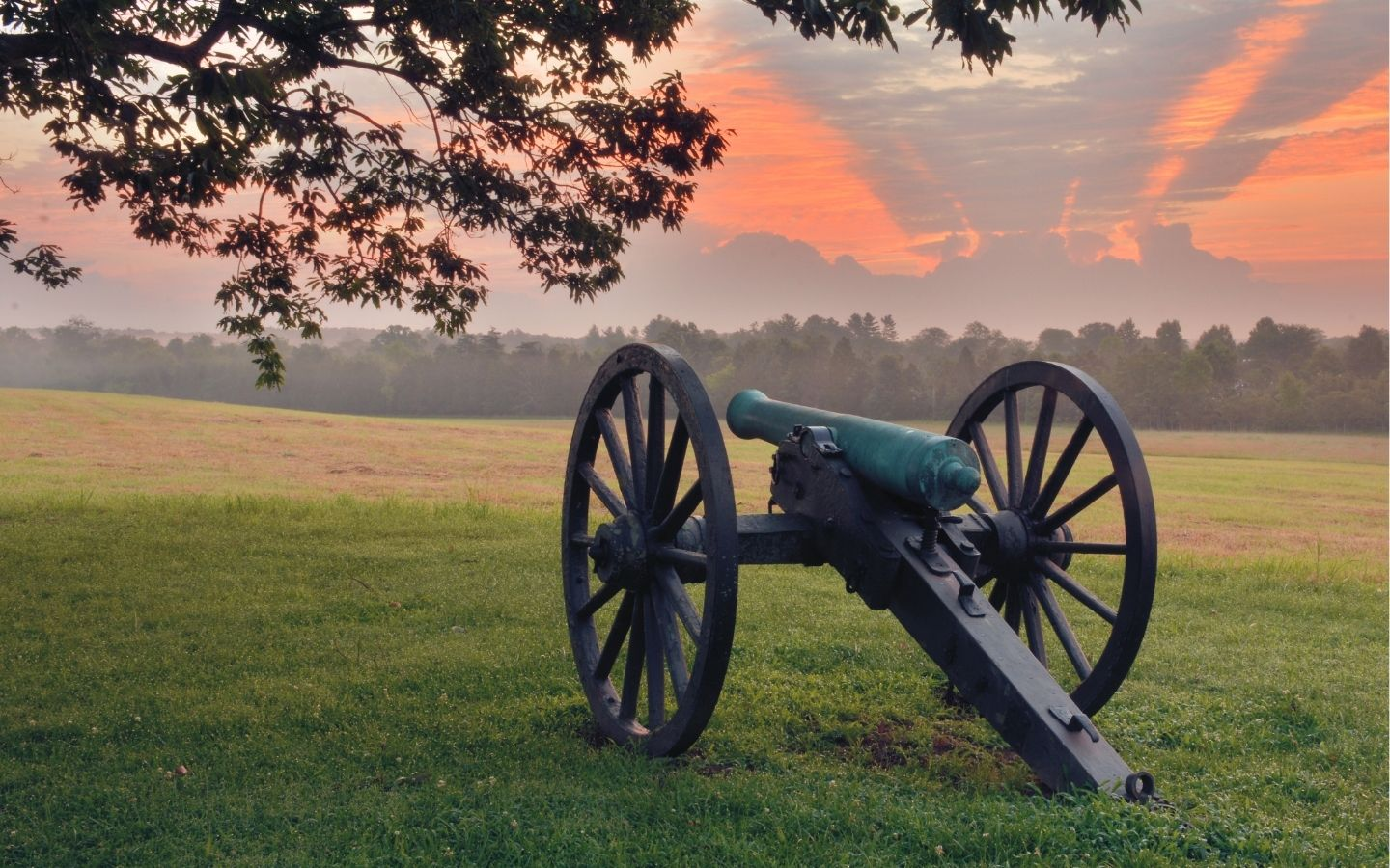 Civil war cannon in the grass amidst a sunset sky