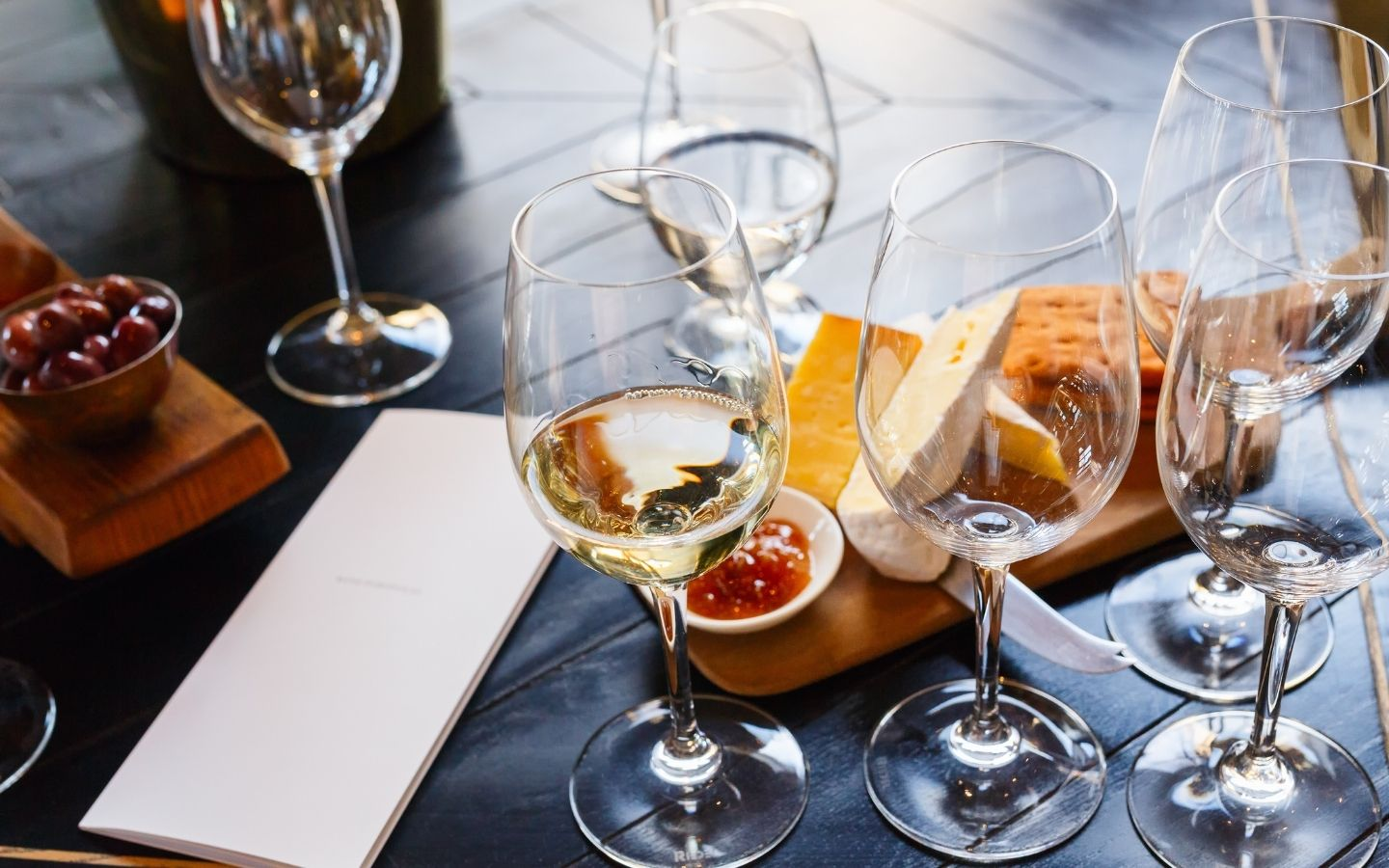 Table topped with assorted wine glasses, fruit, cheeses and breads for tasting